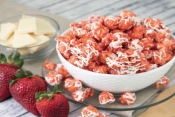 Poppin Popcorn Strawberry Shortcake in a white bowl with strawberries and cream cheese slices